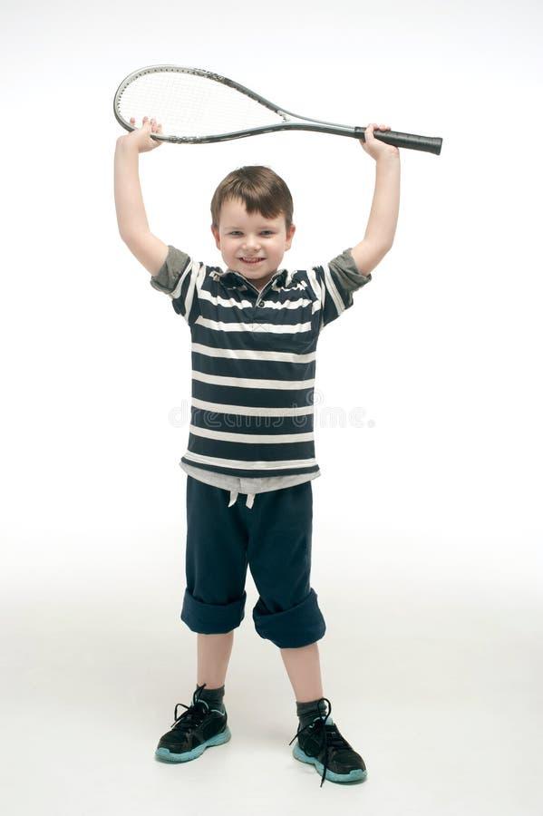 有网球拍的小男孩 免版税图库摄影