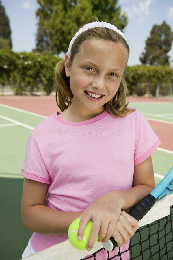 有网球拍的由网的女孩和球在网球场画象 免版税库存照片