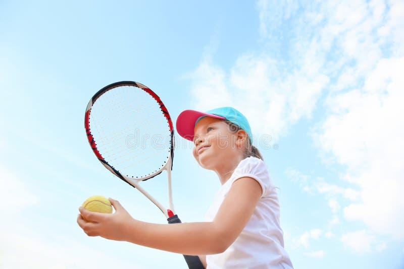 有网球拍的逗人喜爱的反对天空的小女孩和球 免版税图库摄影