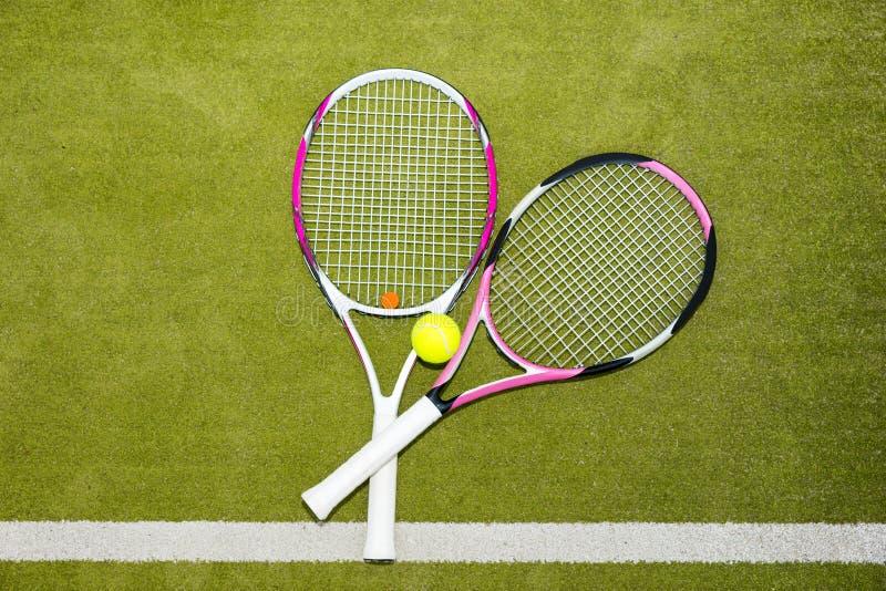 有网球的两个新的桃红色网球拍在绿草 免版税图库摄影