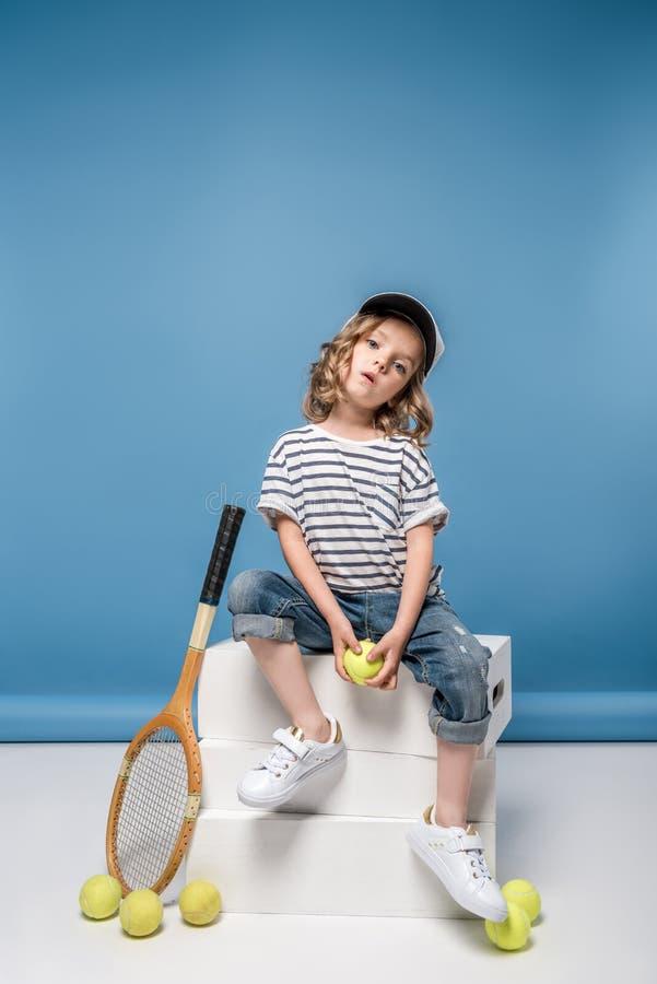 有网球设备藏品的美丽的白肤金发的小女孩 免版税图库摄影