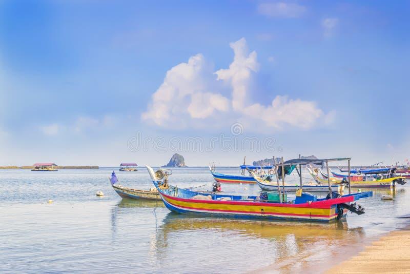 有网的传统亚洲渔船停放在离海岸的附近在去的钓鱼在与云彩的天空蔚蓝背景前 免版税库存图片