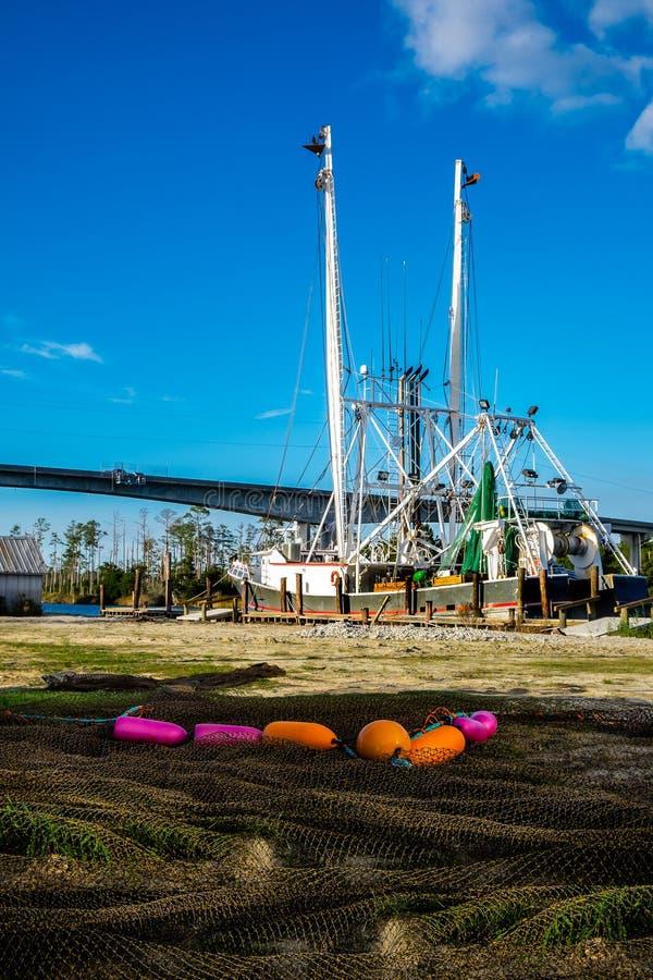 有网的拖网渔船在沿海运河漂浮 库存照片