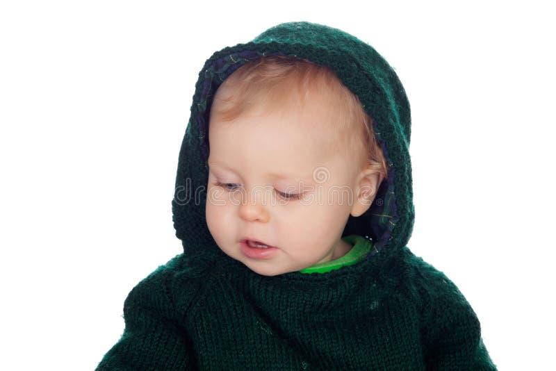有羊毛报道他的头的球衣有冠乌鸦的可爱的白肤金发的婴孩 免版税库存图片