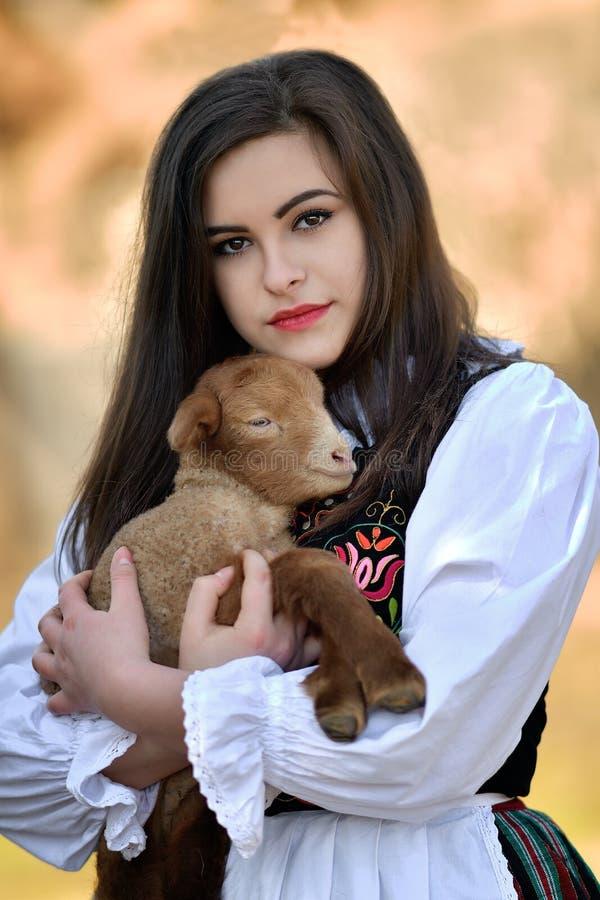 有羊羔和传统服装的罗马尼亚美丽的女孩 免版税库存图片