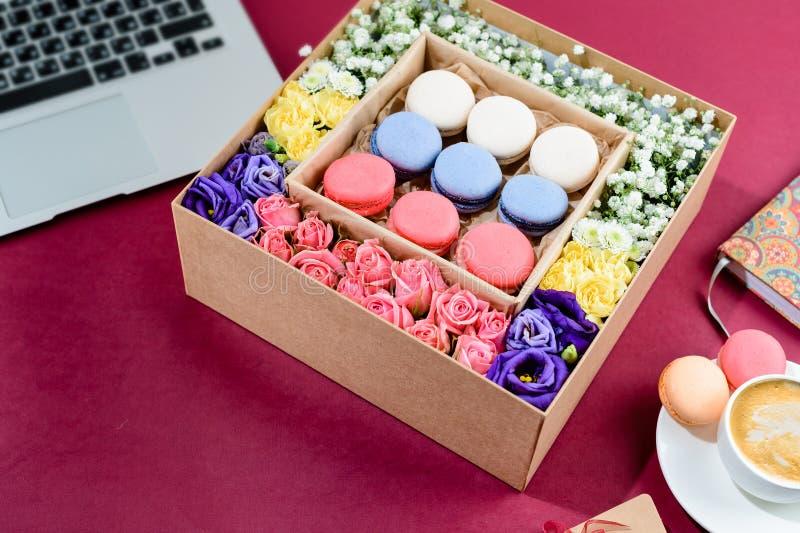 有美丽的五颜六色的花和蛋白杏仁饼干的箱子 免版税库存照片