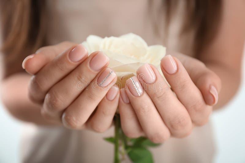 有美丽的修指甲藏品玫瑰的,特写镜头年轻女人 库存图片
