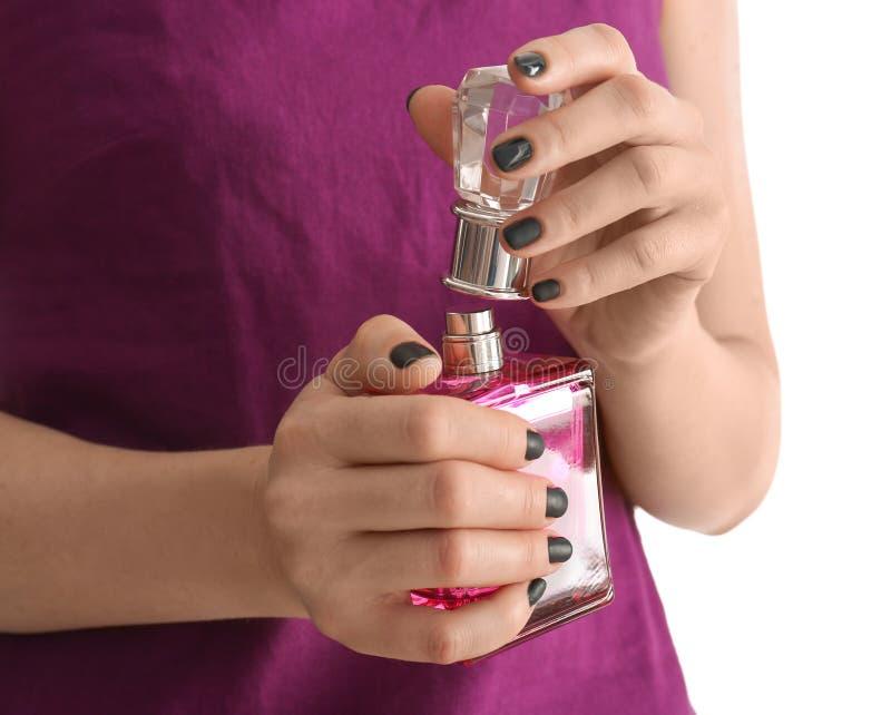 有美丽的修指甲藏品瓶的年轻女人在白色背景,特写镜头的香水 免版税库存图片