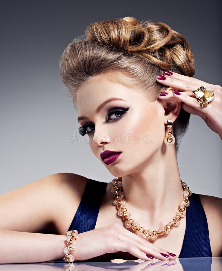 有美丽的发型和金首饰的,明亮的m俏丽的女孩 免版税库存图片