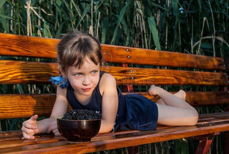 有美丽的大蓝眼睛的一个小女孩在与一个碗的长凳说谎在她前面的新blachberries 免版税库存照片