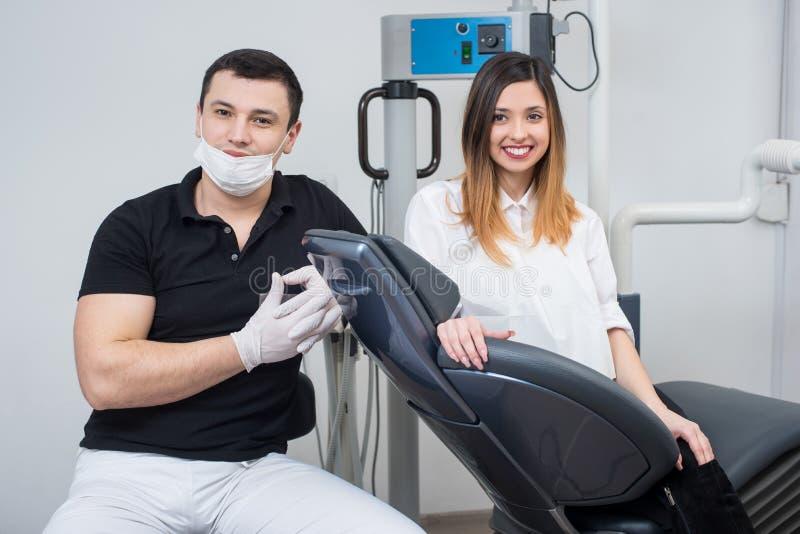 有美丽的女性患者的英俊的男性牙医在治疗以后在现代牙齿办公室 图库摄影