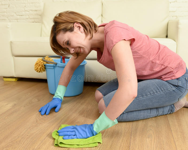 有美丽的微笑清洁房子洗涤的地板下跪的愉快的主妇妇女 免版税库存照片
