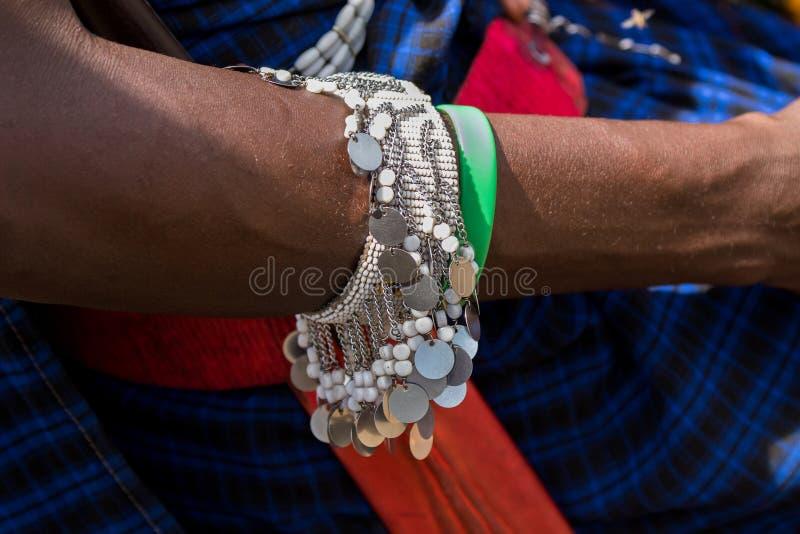 有美丽的手工制造银色手镯的Maasai非洲man's腕子在阿鲁沙,坦桑尼亚,非洲 免版税库存图片