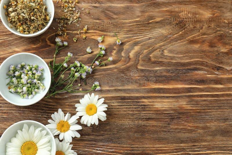 有美丽的新鲜和干燥春黄菊的碗在木背景 库存照片