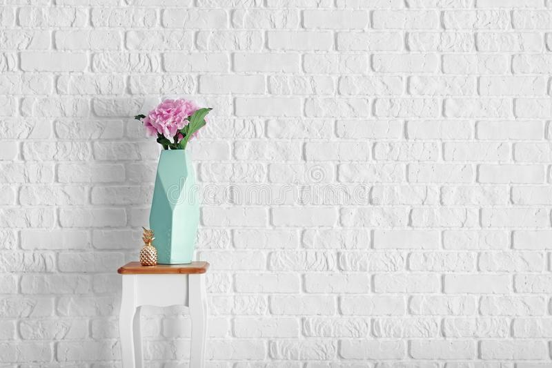 有美丽的桃红色花的花瓶在白色砖墙附近的凳子 图库摄影