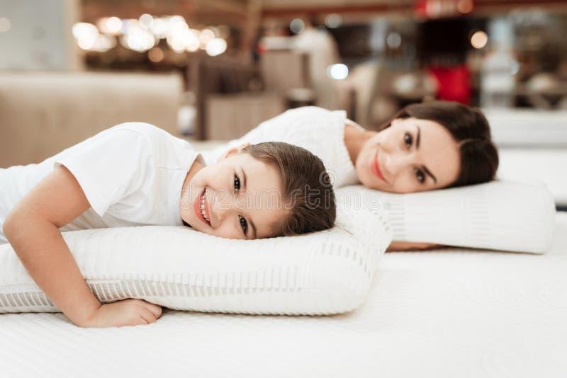 有美丽的母亲的微笑的小女孩在矫形床垫商店拥抱枕头 库存照片