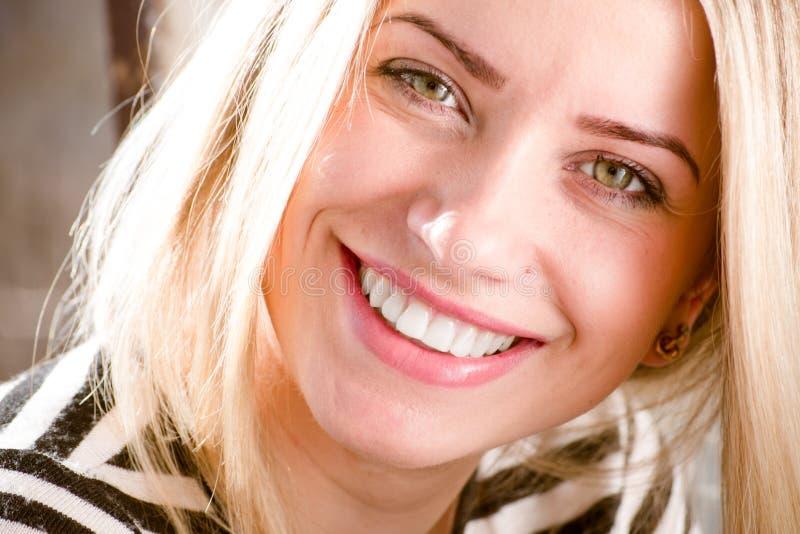 有美丽的白肤金发的少妇的特写镜头图片乐趣愉快的微笑的显示的伟大的牙齿漂白的牙 库存照片