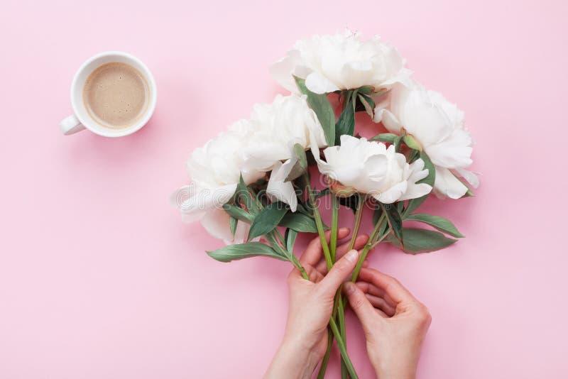 有美丽的白色牡丹花和咖啡的妇女手在桃红色淡色台式视图的 在平的被放置的样式的早餐 免版税库存照片