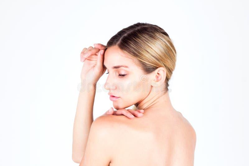 有美丽的看下来和接触她的前额的皮肤和赤裸后面的少妇 免版税库存图片