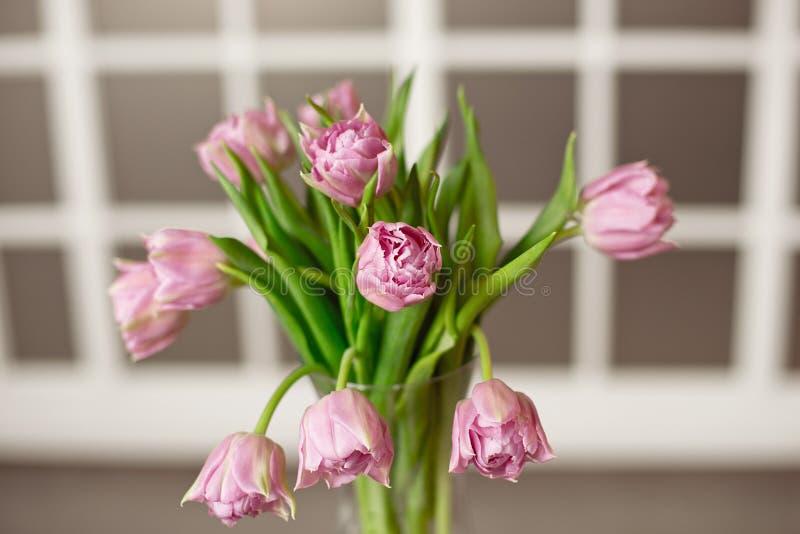 有美丽的紫色郁金香花束的玻璃花瓶以污迹玻璃窗为背景的 免版税库存图片