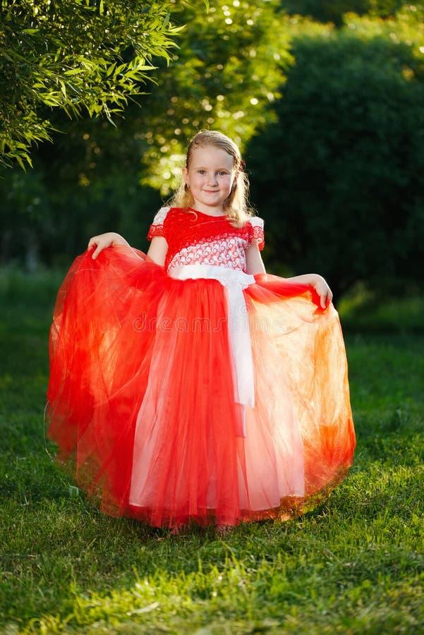 有美丽的红色礼服的女孩在公园 免版税库存图片