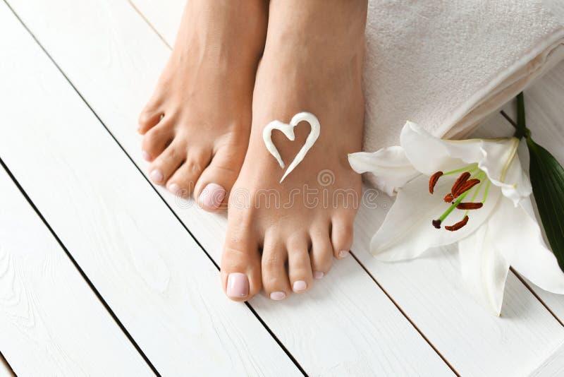 有美丽的脚、奶油、花和毛巾的妇女在白色木地板,特写镜头上 图库摄影