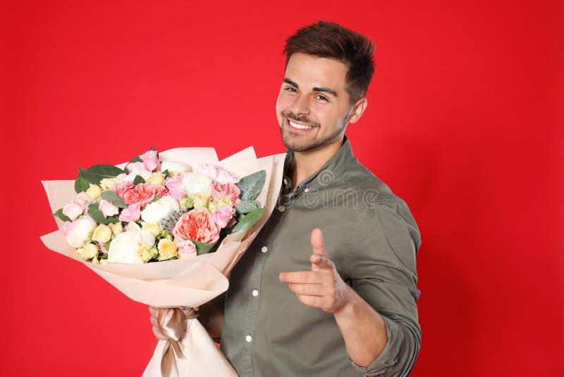 有美丽的花束的年轻帅哥在红色背景 图库摄影