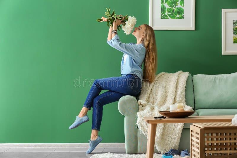 有美丽的花的可爱的年轻女人在家坐沙发 免版税库存照片