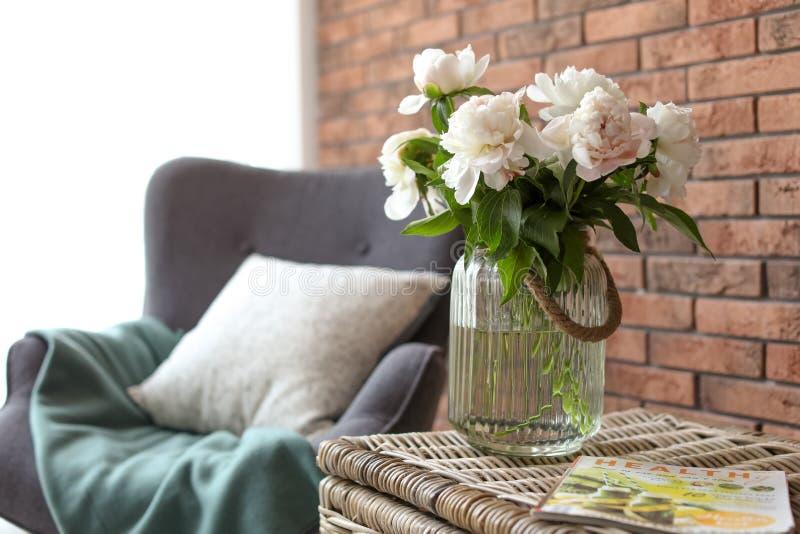 有美丽的花的花瓶在柳条树干,户内 内部装饰元素 免版税库存图片