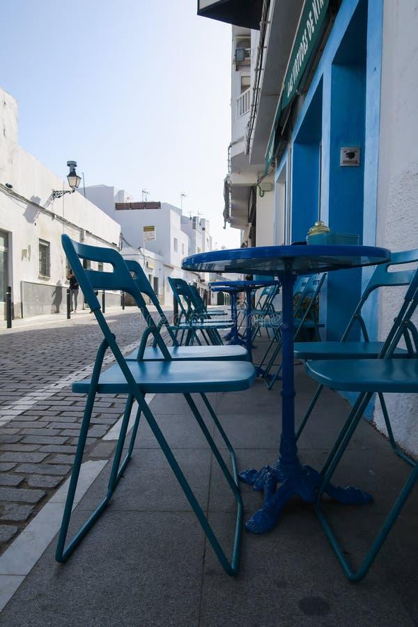 有美丽的蓝色椅子的咖啡馆和桌在一小镇在南西班牙 库存照片