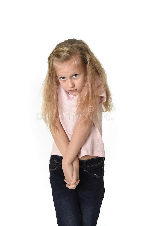 有美丽的金发的甜小孩女孩在看起来的便衣害羞和怯懦,好象惊吓 免版税库存图片