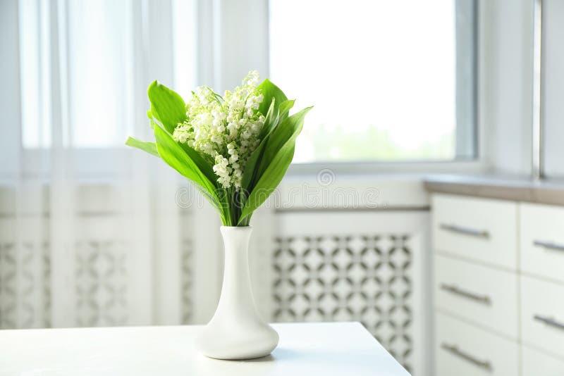 有美丽的铃兰花束的花瓶在桌上在屋子里 免版税库存图片