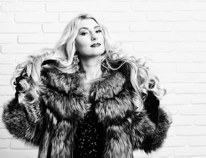有美丽的长的卷曲金发的年轻时兴的性感的相当富有的妇女在灰色毛皮和黑色腰部外套  免版税库存照片