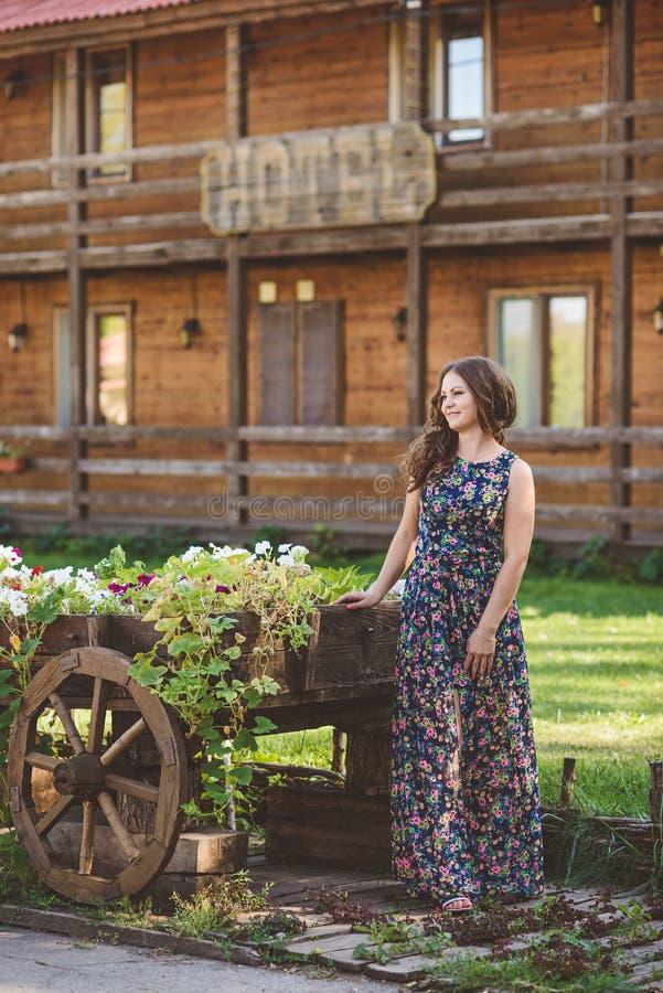 有美丽的长的头发的少妇在装饰木推车附近的花服有花的,在背景  库存图片