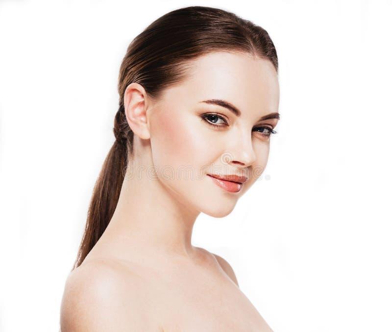 有美丽的面孔、健康皮肤和她的头发的妇女在画象演播室的后面关闭白色的 库存照片