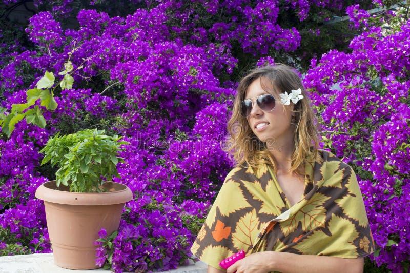 有美丽的紫色花围拢的太阳镜的女孩 库存照片