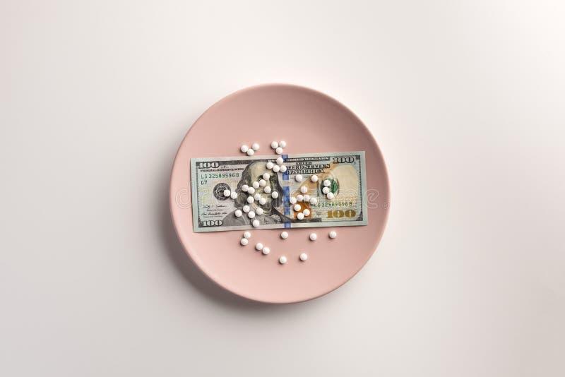 有美元钞票的一块在白色隔绝的板材和药片 库存图片
