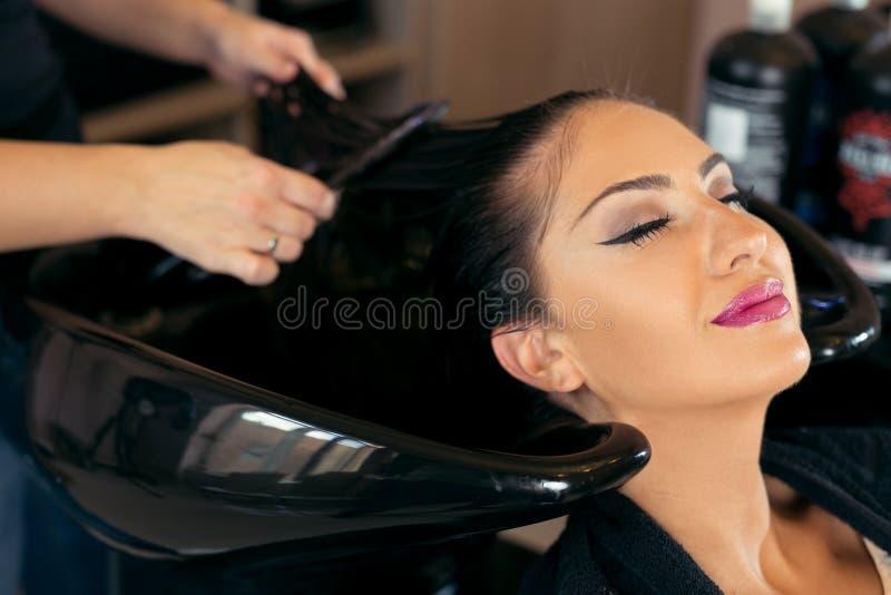 有美发师洗涤的头的美丽的少妇在发廊 库存图片