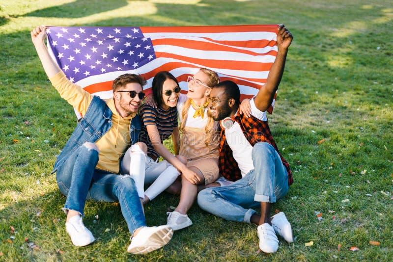 有美国国旗的多种族快乐的朋友坐绿草 免版税库存照片