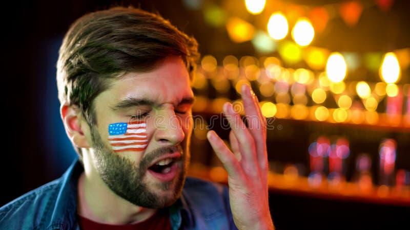 有美国国旗的急切足球迷在面颊生气与比赛结果 免版税库存图片