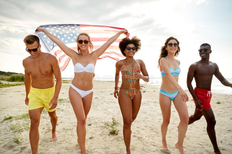 有美国国旗的愉快的朋友在夏天海滩 免版税库存图片