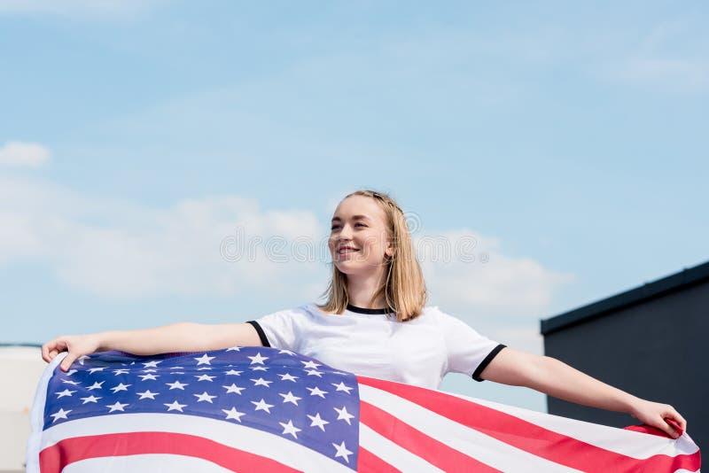 有美国旗子的微笑的青少年的女孩在前面 免版税库存图片