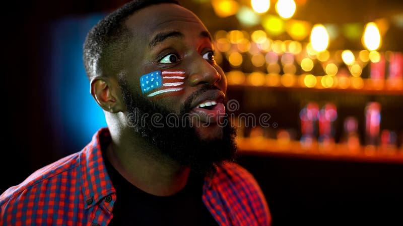 有美国旗子的急切黑人在电视的面颊观看的体育竞赛在酒吧 免版税库存图片