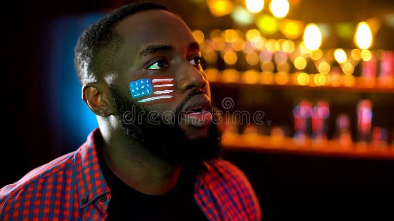 有美国旗子的被集中的非裔美国人的人在酒吧的面颊观看的新闻 免版税库存照片