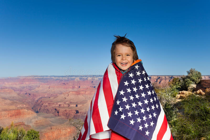 有美国旗子的,大峡谷快乐的小男孩 库存图片