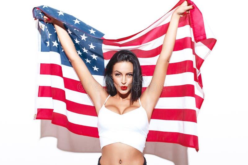 有美国的性感的深色的妇女下垂摆在墙壁 库存照片