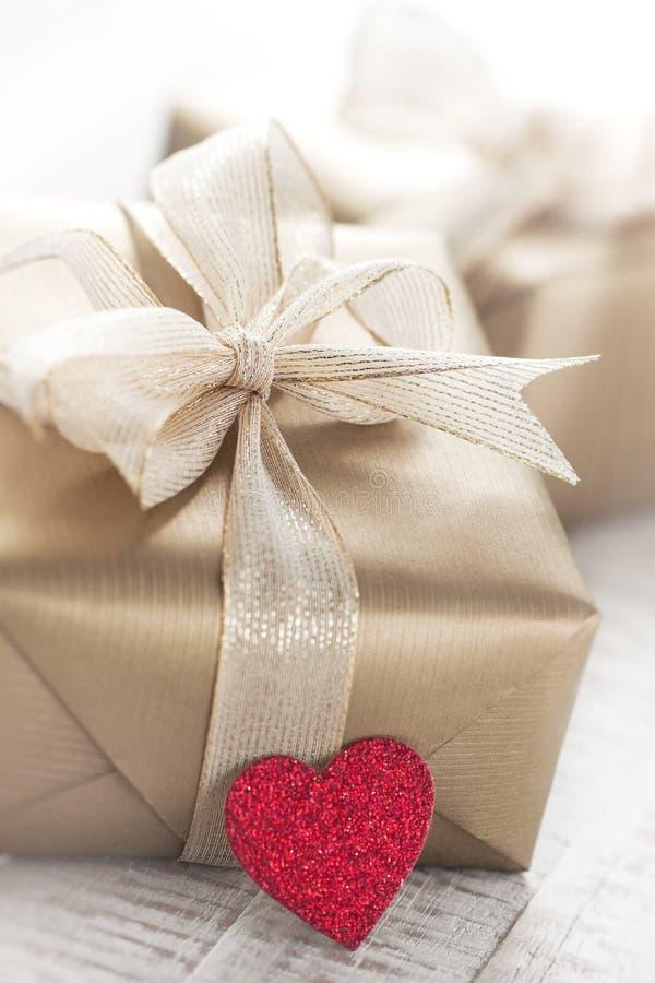 有美好的丝带和弓的金黄礼物盒在明亮的发光的背景 免版税库存图片