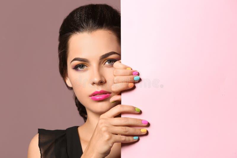 有美好的修指甲和空白的海报的美丽的年轻女人在颜色背景 免版税图库摄影