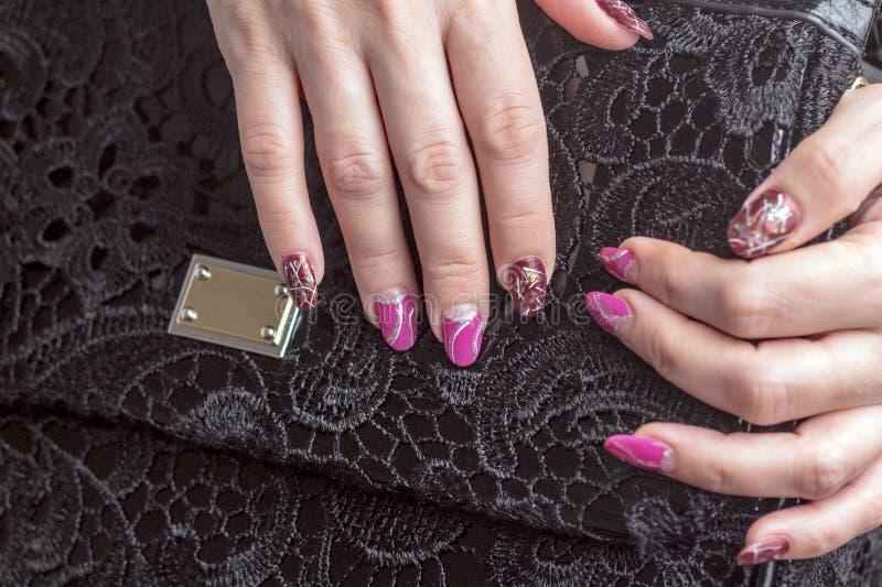 有美好的修指甲的女性手在与鞋带的一个黑袋子说谎 免版税库存照片