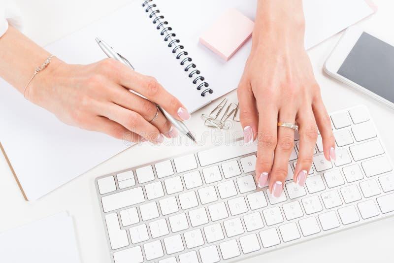 有美好的修指甲的年轻女实业家键入在键盘的在工作场所 免版税库存图片
